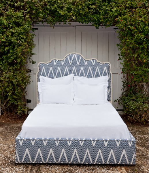 blue and white geometric fabric bed with white wood accents