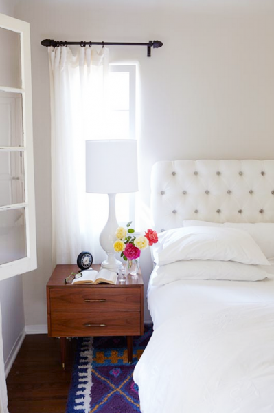 White tufted headboard with white bedding but bight rug.