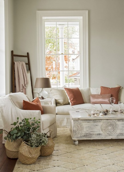cream colored, slip covered furniture with coaral pillows. Baskets of flowers and white wash wooden coffee table trunk.