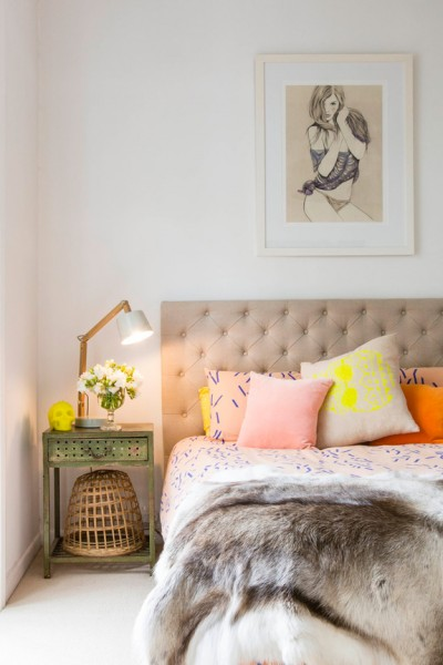 tan tufted headboard with neon pillows