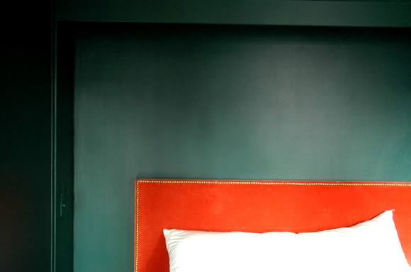 orange velvet headboard with forest green walls
